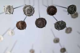A variety of old coins hanging from wires