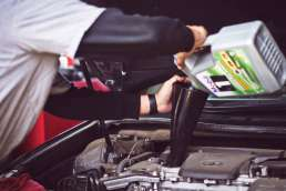 Man working on car adding oil to the engine