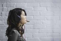 Woman wearing headset facing right against a white brick background