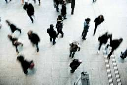 Birdseye view of many people walking on a gray tile floor