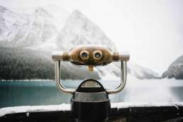 Mounted binoculars facing the snowy mountains across the lake in the background