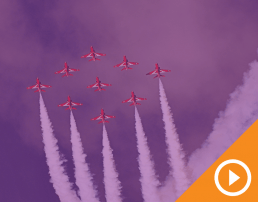 Nine planes flying in formation across the sky behind a purple transparency with a white play button on an orange triangle in the bottom right corner