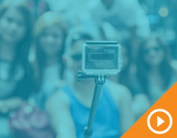GoPro on selfie stick with blurry crowd in background behind blue transparency with white play button on an orange triangle in the bottom right corner