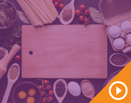 Cutting board surrounded by ingredients behind purple transparency with white play button on an orange triangle in the bottom right corner