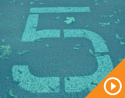 Number 5 painted on concrete behind a blue transparency with a white play button on an orange triangle in the bottom right corner