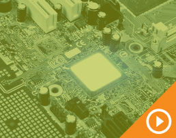 Close up photo of a circuit board behind a green transparency with a white play button on an orange triangle in the bottom right corner