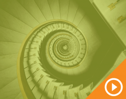 Birdseye view of a spiral staircase behind a green transparency with a white play button on an orange triangle in the bottom right corner