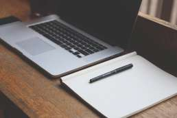 Blank laptop and notebook with pen sitting on wooden desk