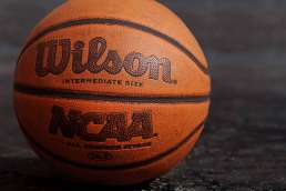 Orange basketball sitting on dark gray concrete