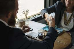 Man and woman shaking hands across a table and coffee