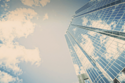 Image of office building reflecting blue sky and white clouds against background of blue sky and white clouds