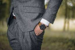 Man in gray suit with a brown watch with his hands in his pockets