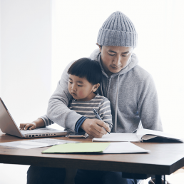 Parent working with child on lap as child plays on laptop