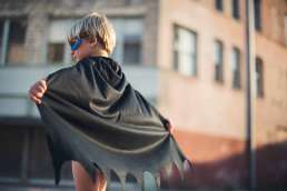 Boy facing away from camera wearing cape and mask with brick building behind him