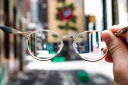 Person holding glasses with blurry street behind them