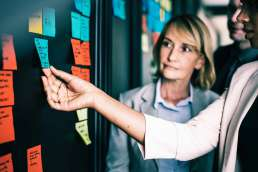 Woman grasping sticky note on wall of with other sticky notes while co-workers look on