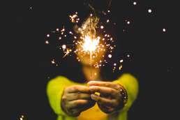 Woman in yellow sweater holding sparkler with black background