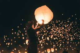 Woman releasing a paper lantern with many other paper lanterns being released into the night sky behind her