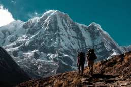 Two people hiking towards mountain with snow and blue sky