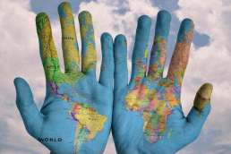 Hands with colorful world map painted on them held up in front of cloudy sky