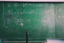 Green chalkboard with equations written on it