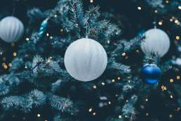 White and blue ornaments on evergreen tree with sparkling lights sprinkled with glitter