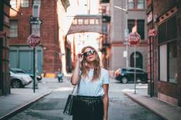 Woman walking down street adjusting sunglasses with brick buildings behind her