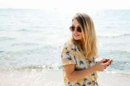 Woman holding phone with ocean behind her