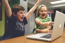 Young boy cheering and girl excitedly pointing at computer screen