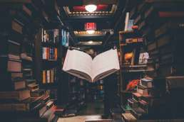 Book floating in bookstore surrounded by other books on shelves