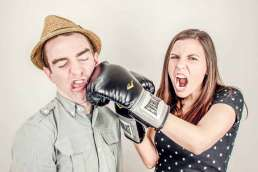 Woman punching man in the face with boxing gloves on