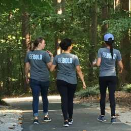 Three women walking with BeBold shirts on