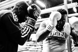 Black and white photo of two men blocking with boxing gloves