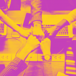 Purple and orange photo of five hands fist bumping over computers