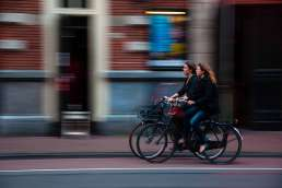 Two women on bicycles in front of a building