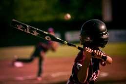 kids' baseball game. child swinging bat at ball.