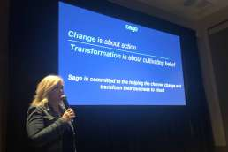 Sage's Kerstin Demko speaking in front of a slide that reads