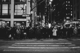 Black and white photo of crowd waiting at a crosswalk