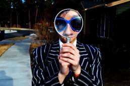 Person in sunglasses holding magnifying glass