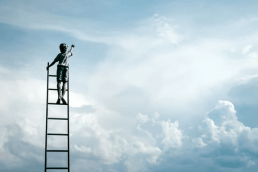 Boy on ladder reaching into cloudy sky